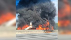 Four people died after a small plane crashed and erupted in flame on I-285 just north of Atlanta, Georgia on May 8, 2015. This photograph shows the plane moments after the crash.